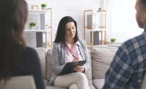 Professional psychologist taking notes at couple meeting with patients
